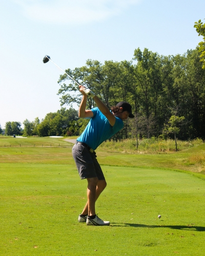 man swinging at golf ball