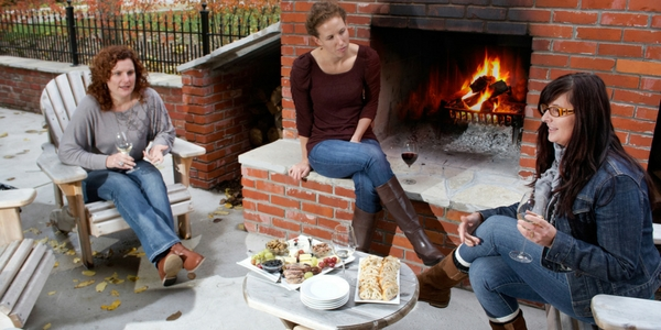Guests sitting at outdoor fireplace holding glasses of wine