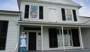 woman in historic dress up standing in front of old white house
