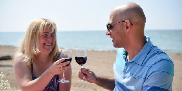 couple enjoying a glass of wine on the beach