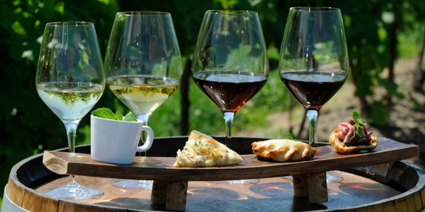 wine glasses and food sample on top of wine barrel in a vineyard